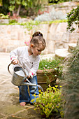 Little girl watering plants with watering can on stone terrace