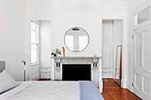 Doppelbett, stillgelegter Kamin, darüber runder Spiegel in weißem Schlafzimmer