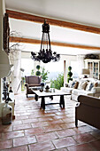 Living room with wrought iron chandelier and terracotta tiles in a French country house