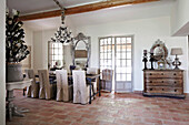 Dining table with hussen chairs and chandelier in a French country house