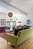 Mischung aus dunklem Leder, lila Samt und lindgrünen Sofas im Wohnzimmer