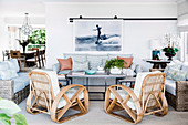 Designer rattan armchairs and sofas around a table in an open living room