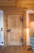 Massivholztür mit Eisenbeschlägen in traditionellem Bauernhaus