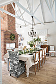 Festively set dining table in front of brick fireplace in high-ceilinged room