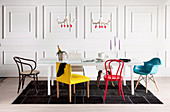 White dining table with various colorful chairs against white wall