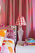 Colorful bed linen, bedside table and table lamp in front of a red and white checkered curtain in the girls' room