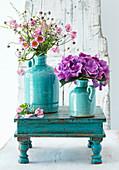 Herbstanemonen und Hortensien in türkisfarbenen Vasen
