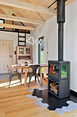 Log-burning stove and dining table in open-plan interior of converted barn