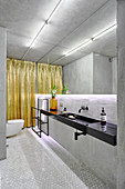 Grey, modern bathroom with indirect lighting on mirrored wall