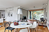 White table and designer chairs in dining area of open-plan interior