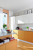 Bright fitted kitchen with island counter in open-plan interior