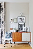 Retro sideboard and chair in corner with black-and-white photographs on wall