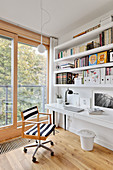 White shelves above white desk and swivel chair with striped upholstery next to balcony doors
