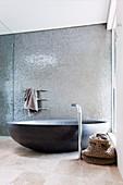 Black oval bathtub against a shimmering silver mosaic wall