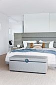 Upholstered chest in front of the bed in the elegant bedroom in white and gray