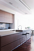 Bar stools on the counter in a modern, minimalist kitchen