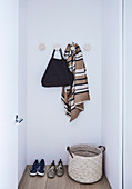 Simple hall coat rack with round wall hooks in a niche