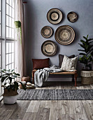 Basket bowls on the gray wall above the bench with pillows