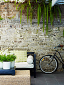 Bench with pad next to bicycle on the terrace, in the foreground plant pots on coffee table