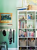 Open shelf on turquoise wall in boy's room