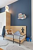 Bett und Kleiderschrank aus Sperrholz an blauer Wand im Kinderzimmer