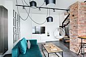 Velvet sofa, plexiglas hanging chair and exposed brickwork in open-plan interior