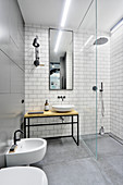 Industrial-style bathroom with metal and tiled walls and shower area behind glass partition