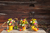 Bouquets of sunflowers and chrysanthemums in vases covered in autumn leaves