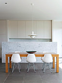 Dining table in front of the marble wall to the open kitchen