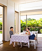 Girl and boy sit at the table on the veranda