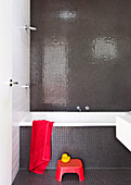 Bathroom with gray mosaic tiles, red stool in front of a bathtub