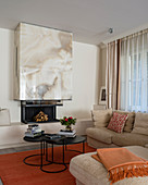 Fireplace with onyx chimney breast in living room decorated in beige and orange