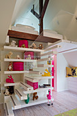 Stairs and shelves leading to gallery in child's bedroom with brightly coloured accessories