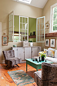 Leopard-print easy chairs in country-house-style study with lattice windows