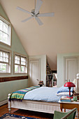 Bedroom with high, sloping ceiling in country-house style