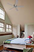 Schlafzimmer mit hoher Decke und Dachschräge im Landhausstil