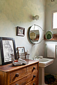 Vintage-style bathroom with painted wall and old wooden chest of drawers