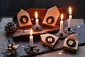 Adventskranz mit nummerierten Papierhäuschen auf Baumrinde und Schieferplatte mit brennenden Kerzen