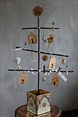 Selbstgebastelter Christbaum aus Ästen mit verschiedenem Christbaumschmuck