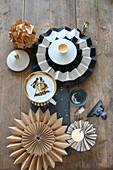 Weihnachtliche Tischdeko mit Vintage-Teller, Papierblumen, Stern und grauen Kerzen auf Schieferplatte