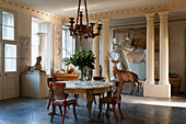 Marble topped table and regency chairs in entrance hall with centaur plaster cast and taxidermy stag