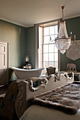 Copper bath in green guest room with crystal chandelier