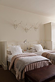 White twin bedroom with mounted antlers, quilts and rugs