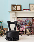 Black easy chair in front of marble fireplace decorated with pictures and sculptures