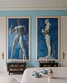 Two large framed photographs of classical sculptures on sky-blue wall