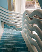 Staircase with sky-blue runner and white, sculptural balustrade