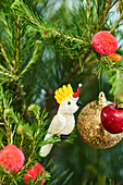 Cockatoo, golden ball, pompoms and apples as Christmas tree decorations