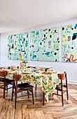 Three-part abstract mural in front of a set dining table with a Mediterranean tablecloth