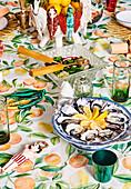 Farbenfroh weihnachtlich dekorierter Esstisch mit mediterranem Obstmotiv-Tischtuch