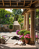 Dogs lying in sunny courtyard with pillars in summery garden